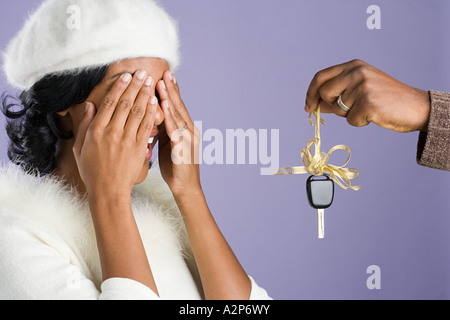 Man surprising woman with gift - Stock Photo