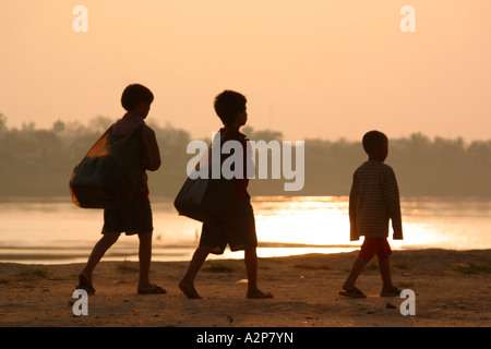 Laos Vientiane sunset on Mekong River three children on riverbank silhouetted against sky - Stock Photo