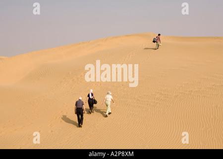 India Rajasthan Thar Desert three older western visitors climbing steep sand dune - Stock Photo