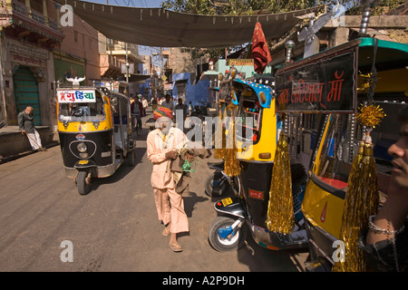 India Rajasthan Jodhpur old city man walking past decorated auto rickshaws - Stock Photo