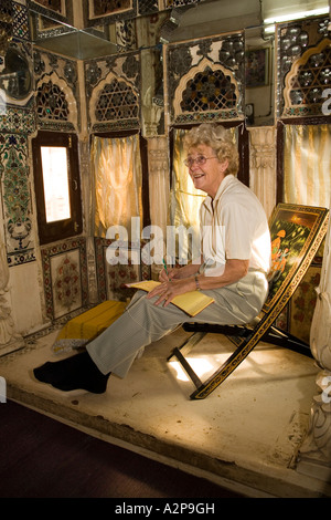 India Rajasthan Jodhpur old city Singhvis Haveli older western woman sitting in bed and breakfast shisha room - Stock Photo