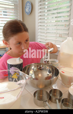 10 year old girl follows a recipe for pancakes She is measuring flour sugar butter milk salt and eggs - Stock Photo