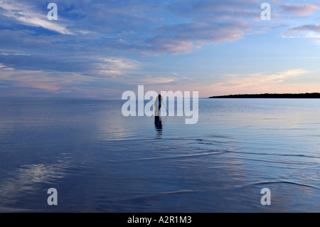 Photographer standing in shallow water at dusk Singing Sands Provinceal Park on Lake Huron Bruce Peninsula Ontario - Stock Photo
