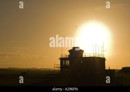 sun setting behind control tower at Duxford air museum as plane lands - Stock Photo