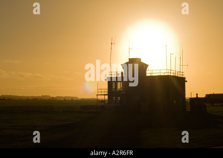 sun setting behind control tower at Duxford air museum - Stock Photo