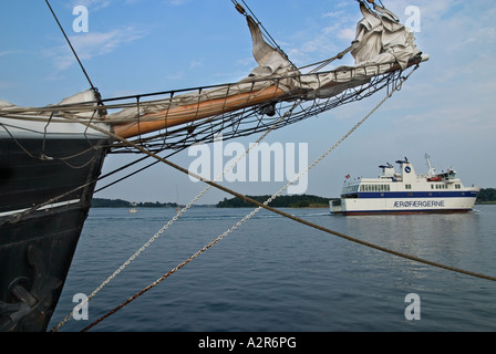 Old Sailing Ships in harbour Svendborg while a small island ferry leave Svendborg fyn Funen Denmark - Stock Photo