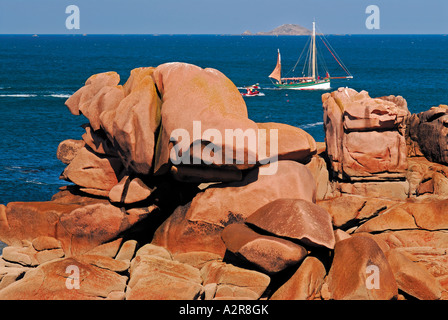 Boat passing in the background, giant pink rocks at front, Ploumanac´h, Cote Granit Rose, Brittany, France - Stock Photo