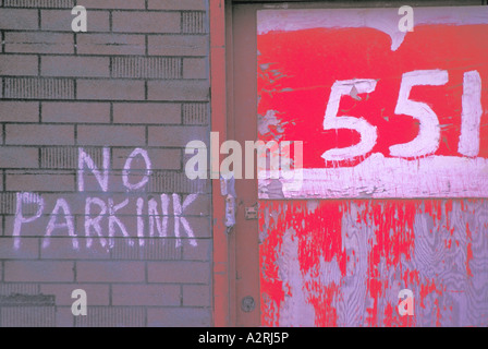 No Parking Sign written on a Brick Wall with Street Address in Red and White - Stock Photo
