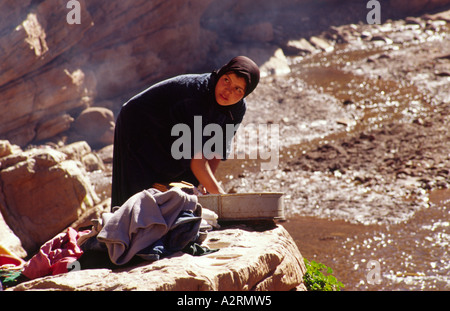 Horizontal portrait of young berber woman washing clothes in the open air by river, High Atlas Mountains, Morocco, - Stock Photo