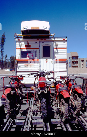 RV Pickup Camper Truck carrying Rowboat on Roof and pulling Trailer loaded with Motocross Dirt Bikes - Stock Photo