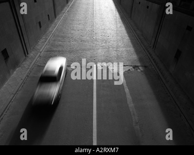 Silver car Mercedes speeding into tunnel Brussels Belgium motion blur monochrome black and white - Stock Photo