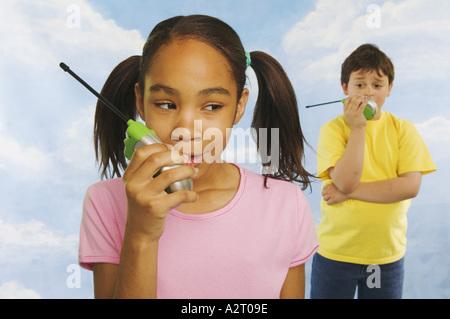 Two kids talking on walkie talkies - Stock Photo