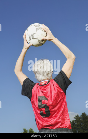 A mature female soccer player throwing the ball in - Stock Photo