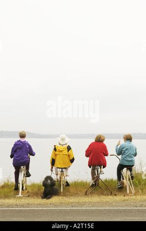 Four women on stationary bikes - Stock Photo