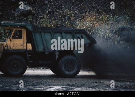 black gold of vietnam large heavy truck deposits fine cloud of black coal dust in its wake as it transports coal - Stock Photo