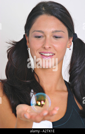 C.U. of young woman almost holding a soap bubble in her hand and looking at it - Stock Photo