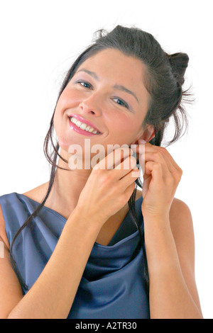M.S. of young woman in blue formal gown looking at the camera and smiling while putting on an earring - Stock Photo