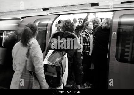 passengers boarding underground train on london underground system - Stock Photo