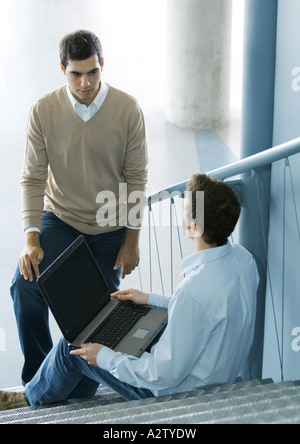 Two male colleagues talking, one sitting on stairs with laptop - Stock Photo