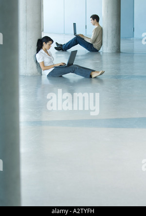 Young woman and man sitting on floor, using laptops - Stock Photo