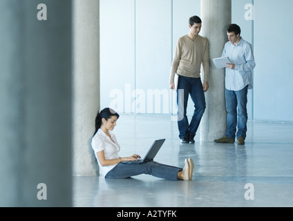Young woman sitting on floor using laptop, two men standing takling about document in background - Stock Photo