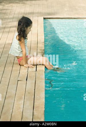 Girl sitting on edge of pool, dangling feet in water Stock Photo