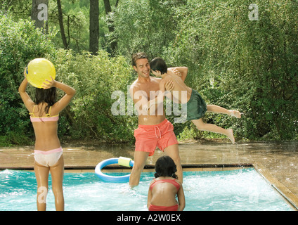 Father and children playing in swimming pool - Stock Photo