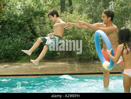 Father throwing son in swimming pool - Stock Photo