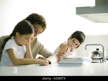Teenage boy helping younger sister with homework, second sibling watching - Stock Photo
