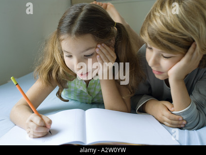 Two children doing homework together - Stock Photo