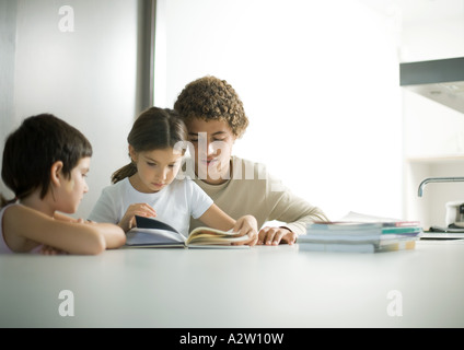 Teenage boy helping younger sister with homework - Stock Photo