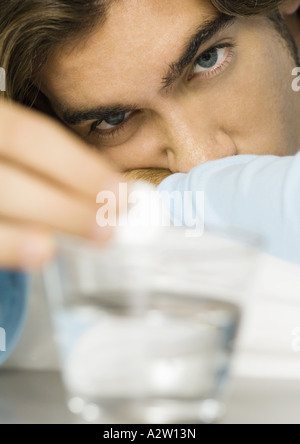 Man putting effervescent medicine into glass of water - Stock Photo