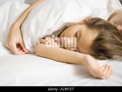 Girl lying in bed with mother's arm around her - Stock Photo