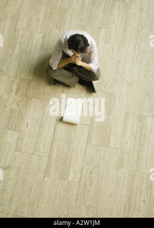 Man sitting on floor with blank pad of paper, high angle view - Stock Photo