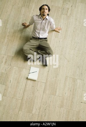 Man sitting on floor with pad of paper in front of him, leaning back, high angle view - Stock Photo