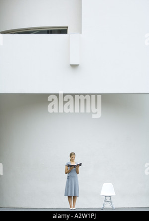 Woman standing next to chair, reading book - Stock Photo