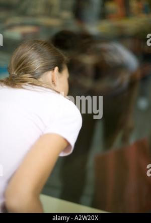 Teenage girl looking into shop window