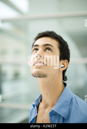 Young man listening to earphones, looking up - Stock Photo
