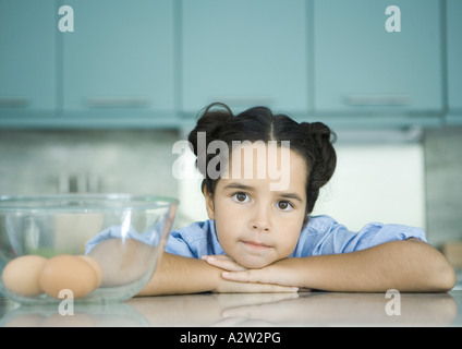 Girl resting head on counter next to bowl containing eggs - Stock Photo