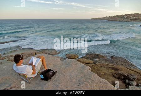 A man relaxing and reading a book on the famous cliffs of Sydney coastline, near Bondi beach, Australia. - Stock Photo