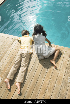 Boy and girl sitting at edge of swimming pool, high angle view - Stock Photo