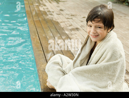 Little boy sitting by edge of swimming pool, wrapped in towel - Stock Photo