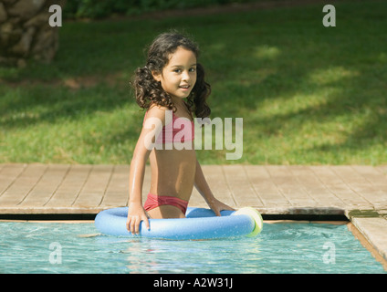 Little girl in swimming pool with floating ring - Stock Photo