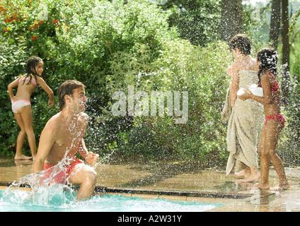 Father splashing children standing around swimming pool - Stock Photo