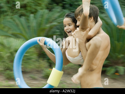 Adolescent boy carrying little sister, holding swimming ring - Stock Photo