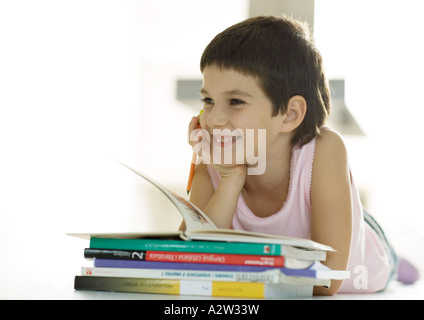 Child lying down next to stack of books, smiling - Stock Photo
