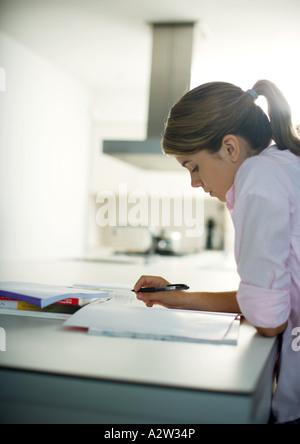 Teen girl doing homework in kitchen - Stock Photo