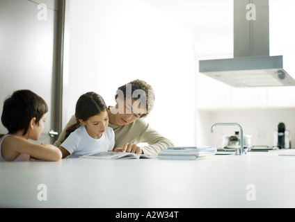 Adolescent boy helping little sister with homework - Stock Photo