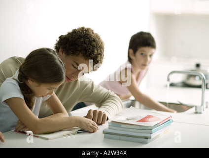 Adolescent boy helping sister with homework - Stock Photo