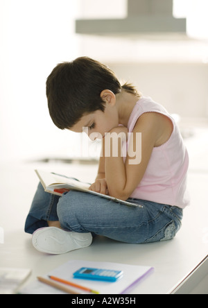 Child sitting on counter reading - Stock Photo